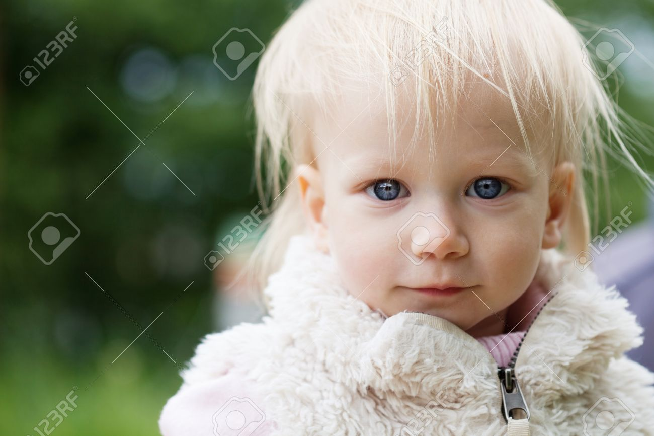 Cute baby girl with blonde hair outdoors. Little girl 1-2 year old,