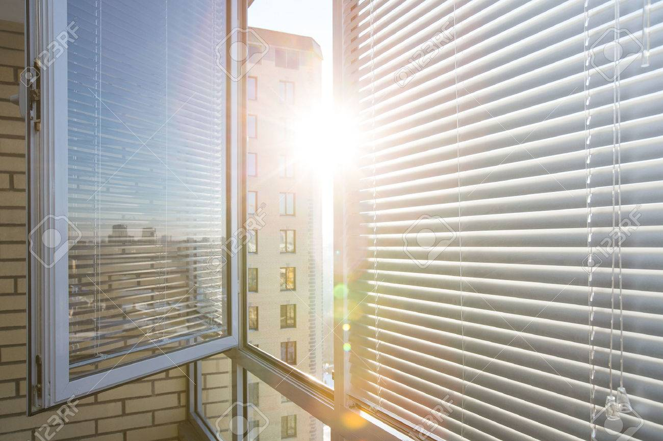 Opened window on sunny day with horizontal plastic blinds - 52823643