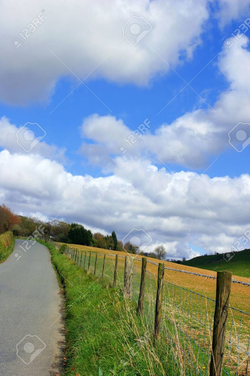 Narrow lane in the countryside with a wooden fence and fields to one side, on a blue sky day with puffy white clouds. Stock Photo - 310687