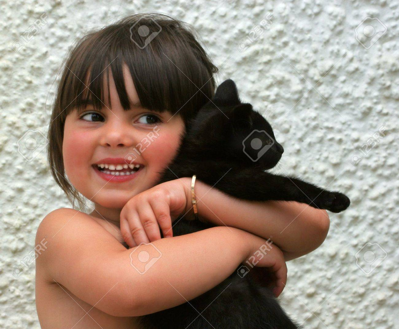 Little girl smiling and holding an all black kitten in her arms. Stock Photo - 333201
