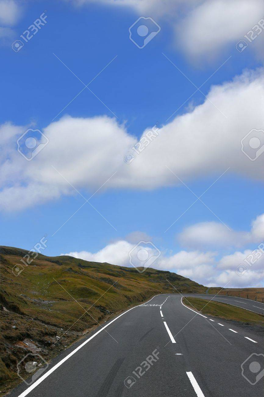 Empty down hill road in mountains with a dangerous right hand bend, with grass verges to either side, on a blue sky day with cumulus clouds. Located in the Brecon Beacons National Park, Wales, United Kingdom, Stock Photo - 607158
