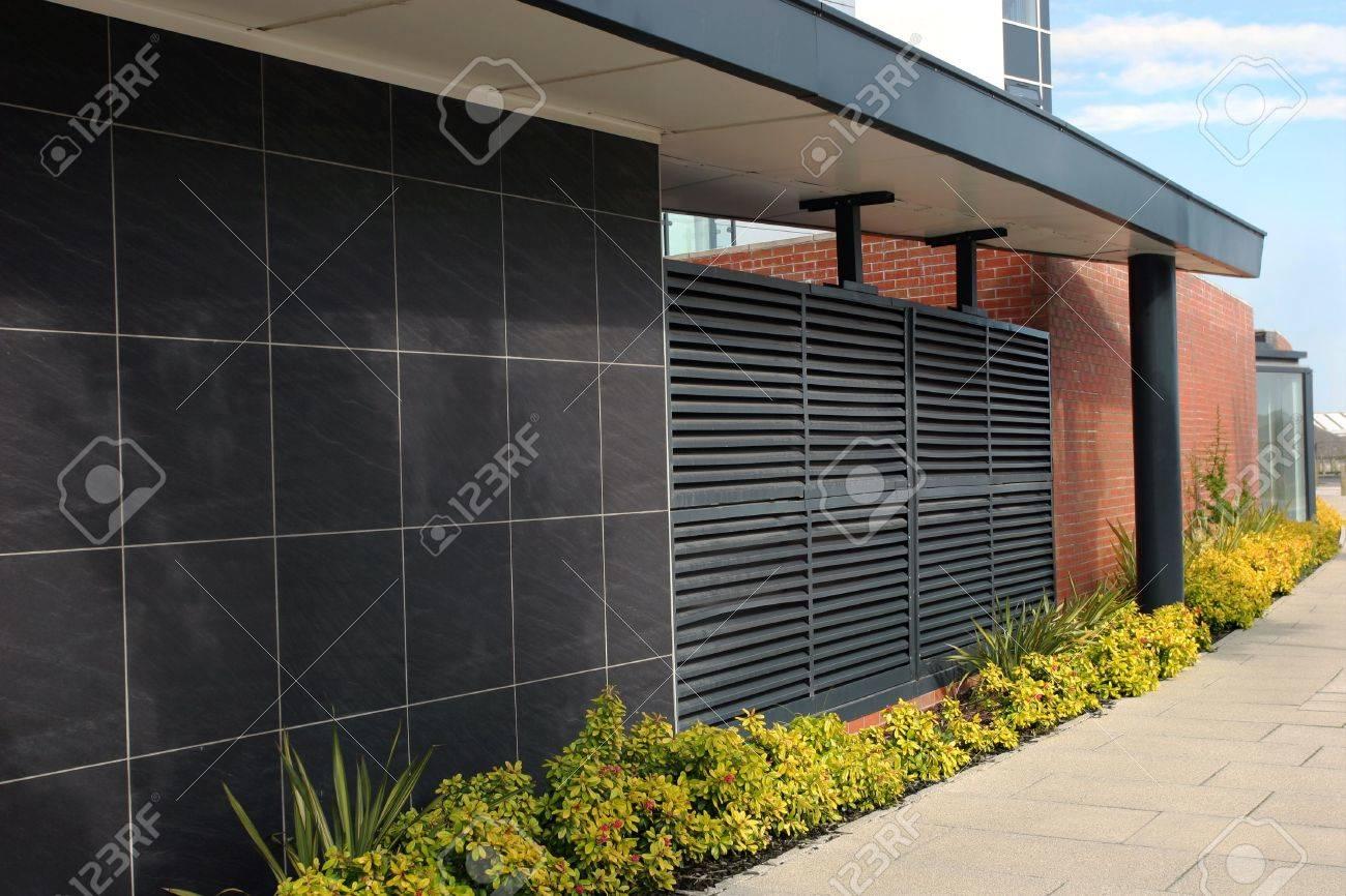 Muro di mattoni rossi curvo con nero assicelle di pannelli di ...