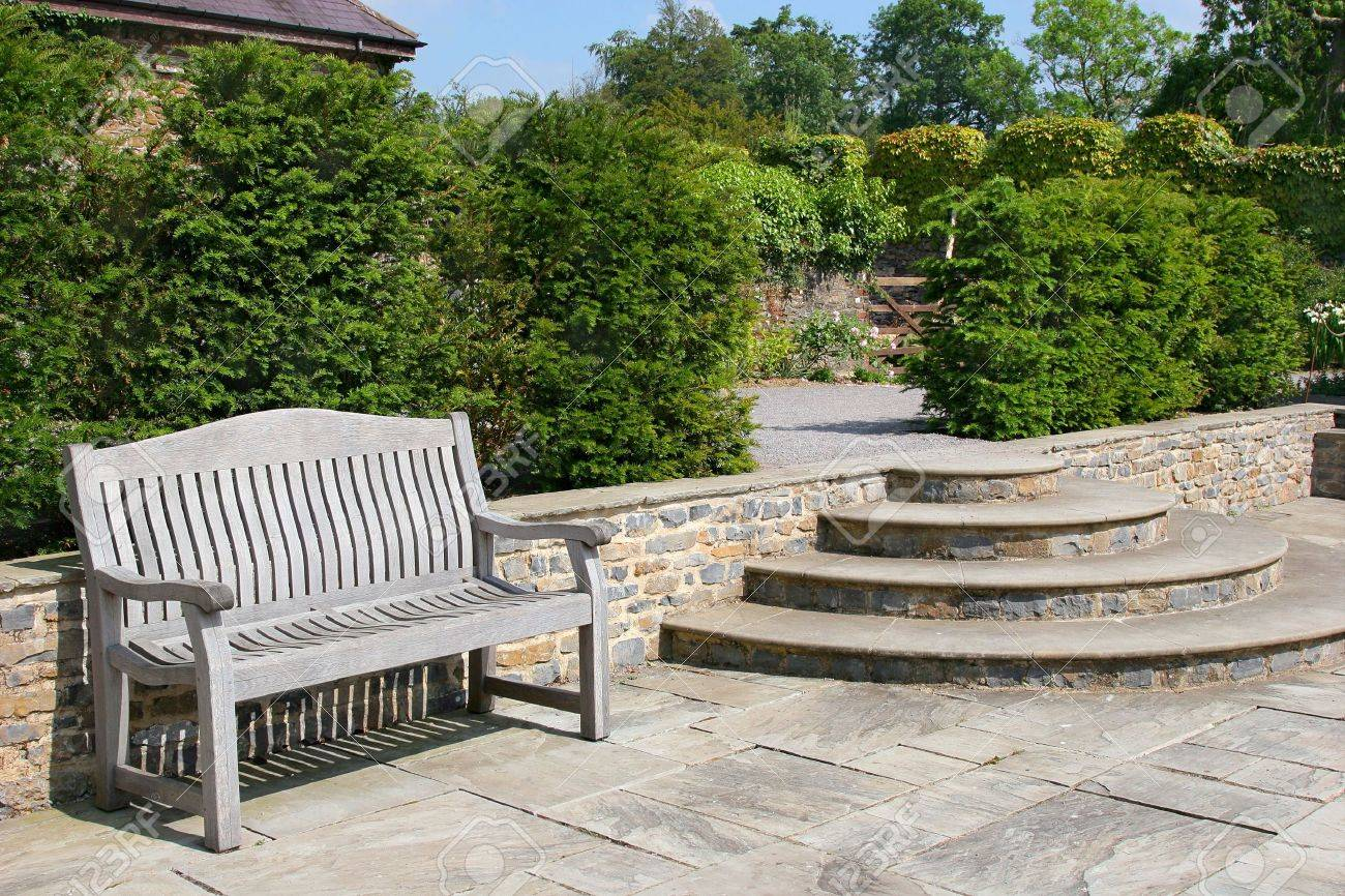Outdoor garden tiled patio area, with an old wooden oak bench, curved steps to the side and shrubs to the rear. Stock Photo - 2807964