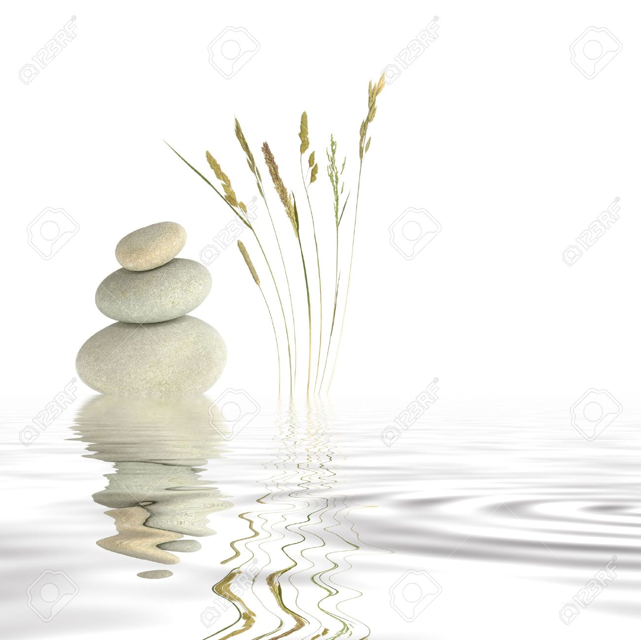 Abstract of three natural grey pebbles balanced on top of each other, with a selection of wild grasses to one side reflected over gray rippled water. Set against a white background. Stock Photo - 3214991