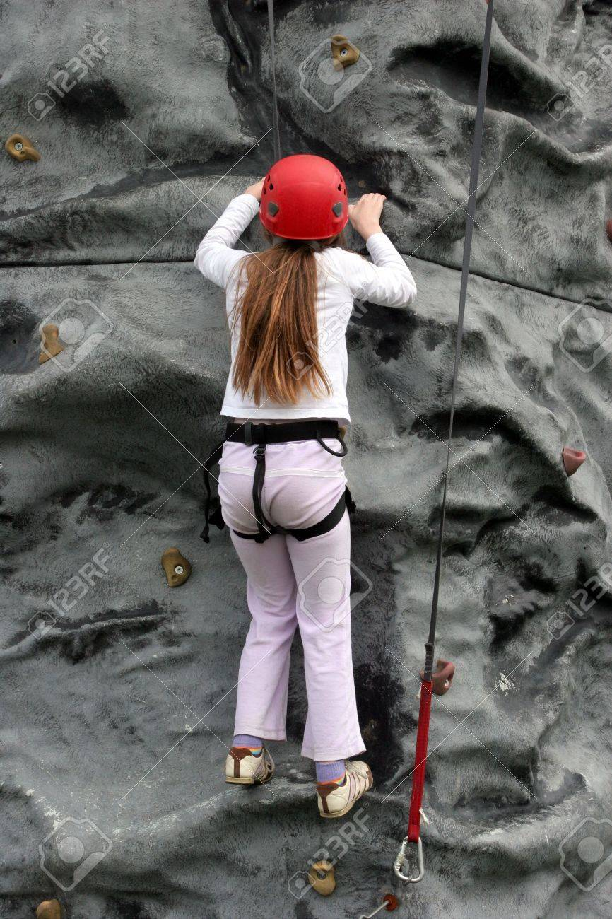 Young girl climbing upwards on a rock training face wearing a safety harness and red hard hat. Stock Photo - 3296497