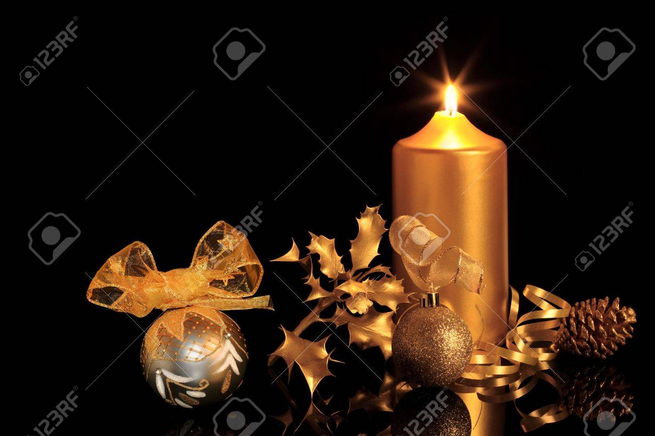 Golden christmas decorations in candlelight including sparkling baubles, ribbon, holly and pine cone, over black background with reflection. Stock Photo - 5487236