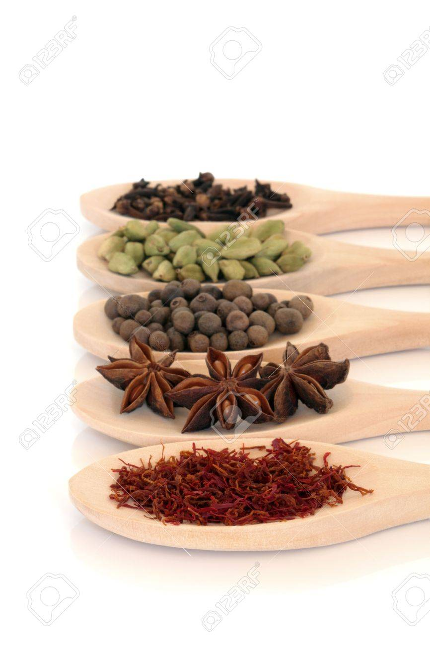 Saffron, star anise, allspice berries, cardamom pods and cloves in wooden cooking spoons, isolated over white background. Focus on the saffron. Stock Photo - 6798145