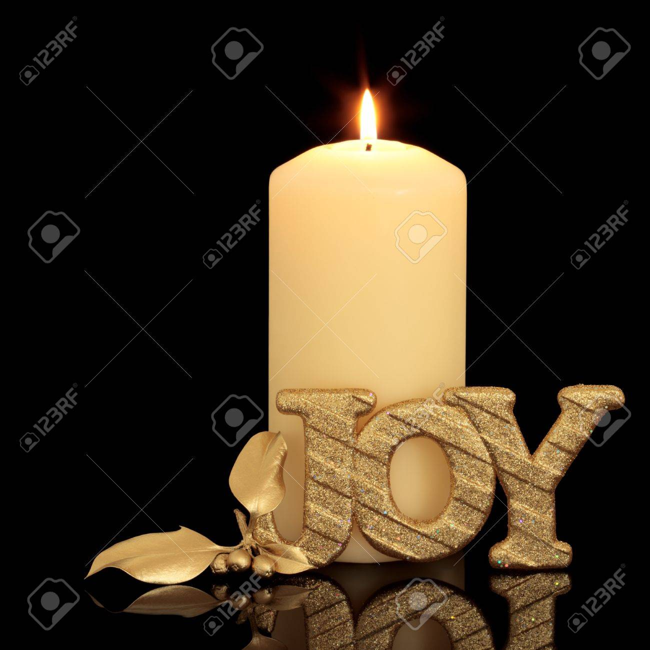 Christmas candle table setting with golden glitter joy sign and holly berry leaf sprig over black background with reflection. Stock Photo - 7903202