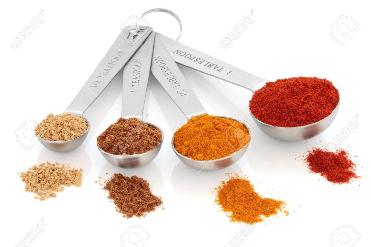 Spice selection of paprika, turmeric, chinese five spice and  ginger in stainless steel measuring spoons, and loose, over white background. Right to left. Selective focus. Stock Photo - 8879220