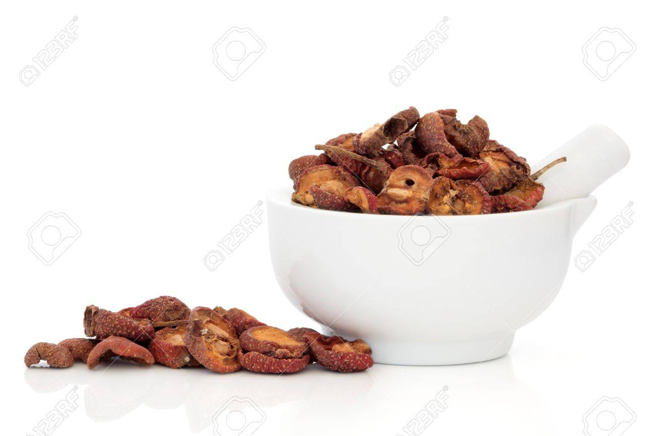 Dried hawthorn fruit used in chinese herbal medicine in a porcelain mortar with pestle and scattered, isolated over white background. Shan zha. Fructus crataegi. Stock Photo - 9709252