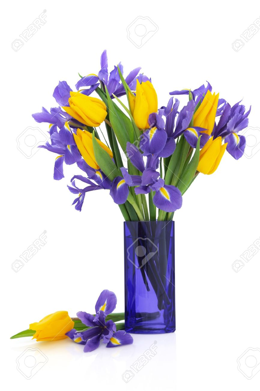 Iris And Yellow Tulip Flower Arrangement In A Blue Glass Vase