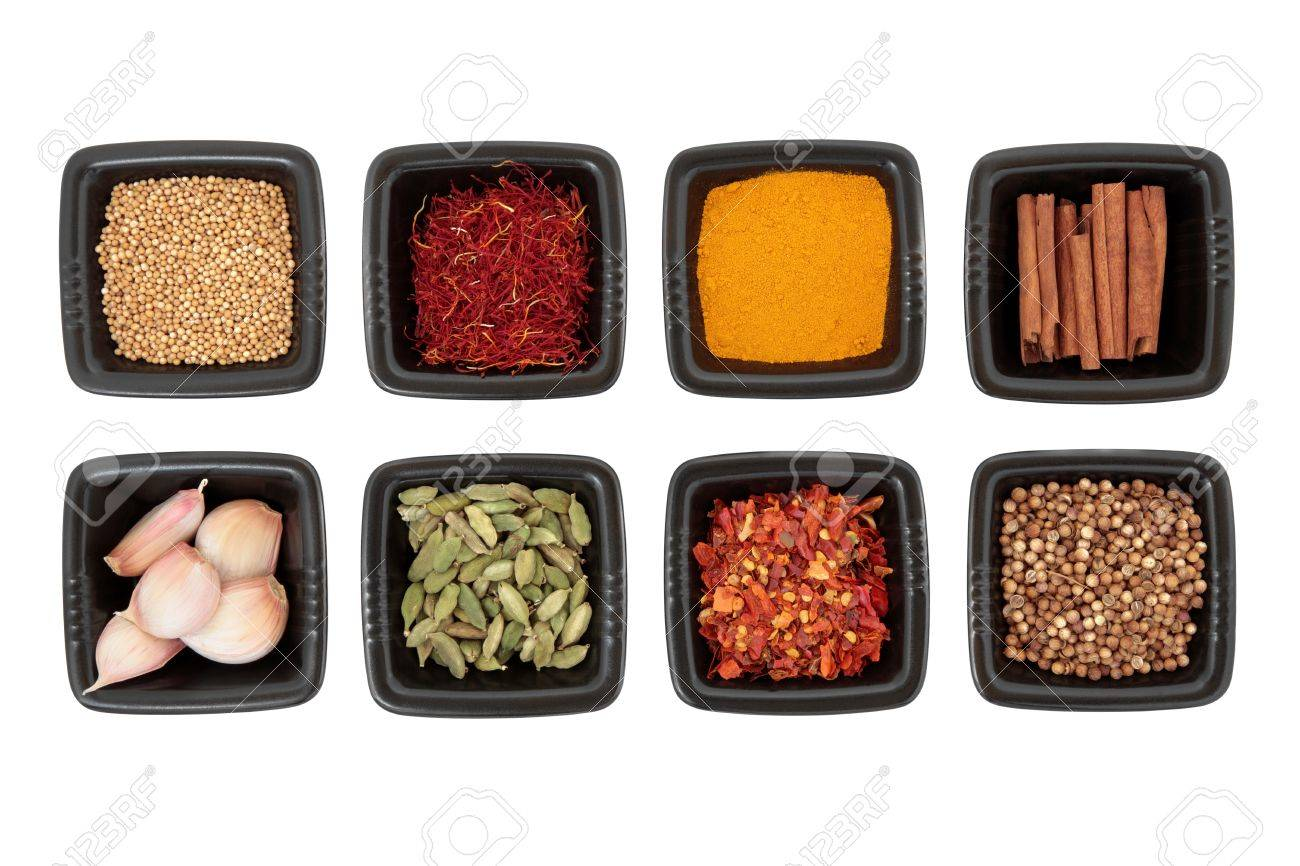 Spice collection of coriander and mustard seed, chili flakes, saffron,  cinnamon sticks, cardamom pods, turmeric, garlic cloves in black square dishes on white background Stock Photo - 14533106