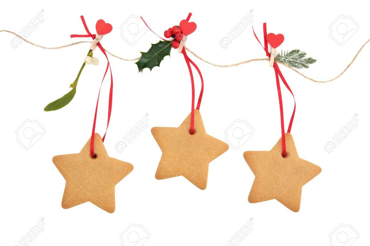Christmas Star Gingerbread Cookies Hanging On A Line With Holly