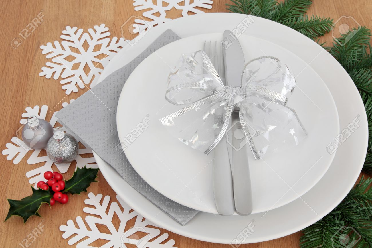 christmas dinner place setting with white plates silver bauble decorations and bow cutlery