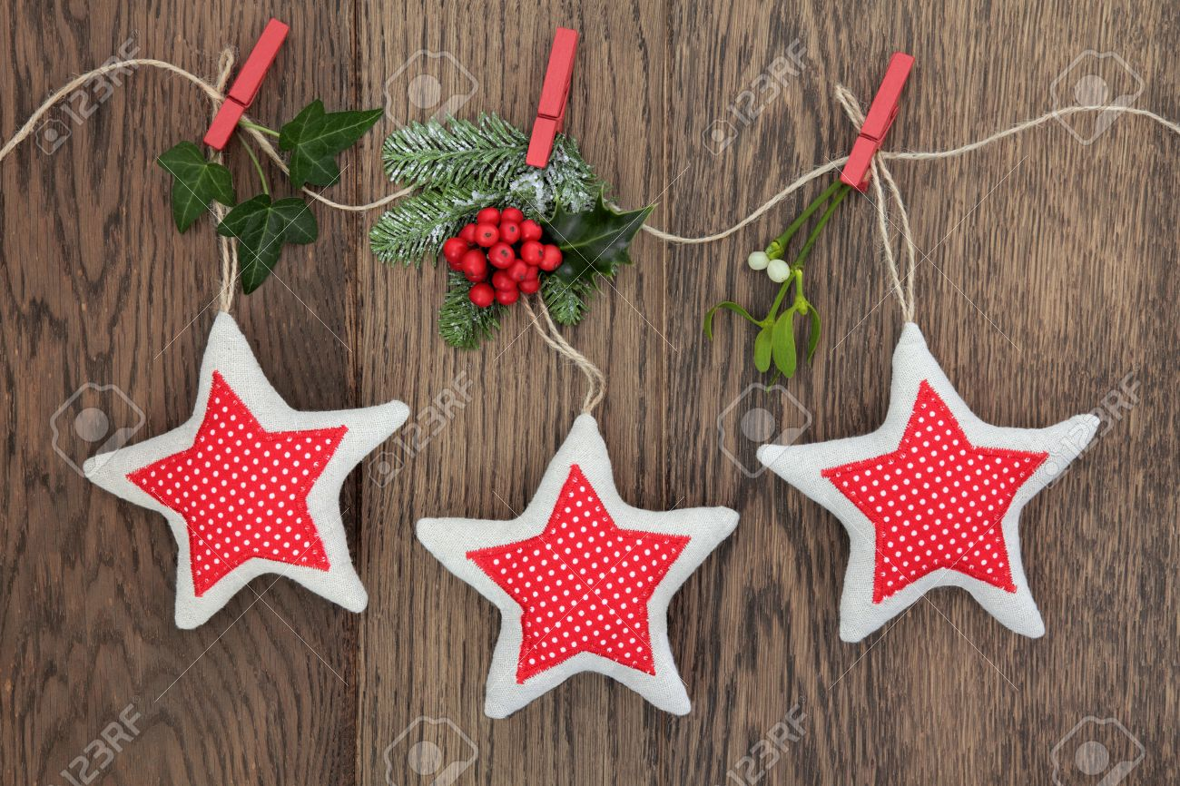 christmas star decorations with holly ivy fir and mistletoe hanging on a string line