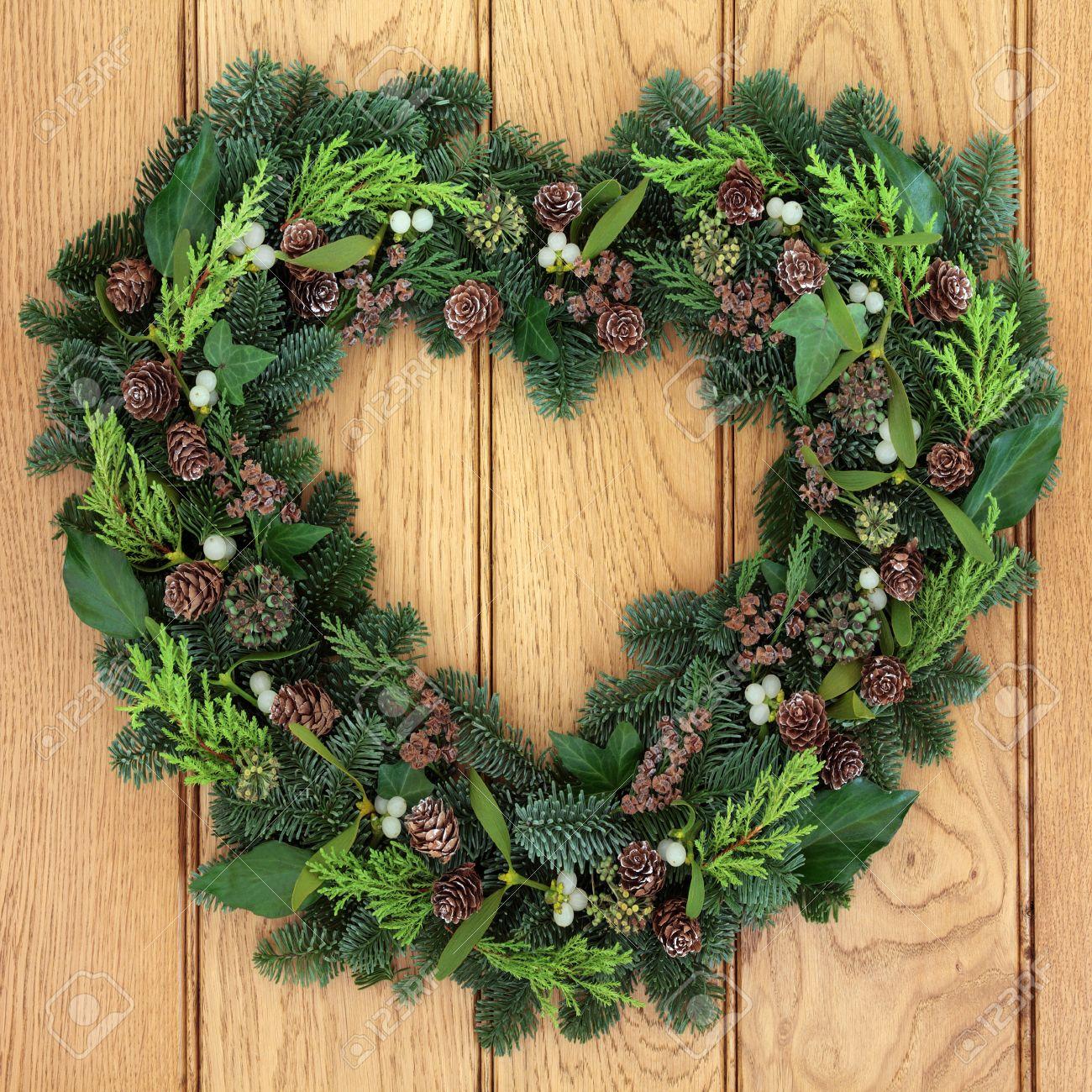 Winter and christmas heart shaped wreath with mistletoe and winter and christmas heart shaped wreath with mistletoe and greenery over oak front door background rubansaba