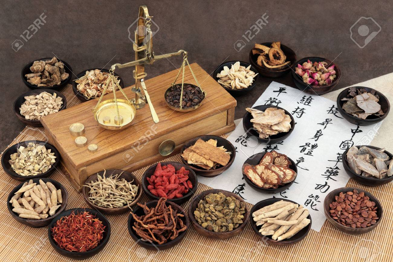 Chinese medicine ingredients with scales and calligraphy on rice paper. Translation read as chinese herbal medicine as increasing the bodys ability to maintain body and spirit health and balance energy. - 52585672