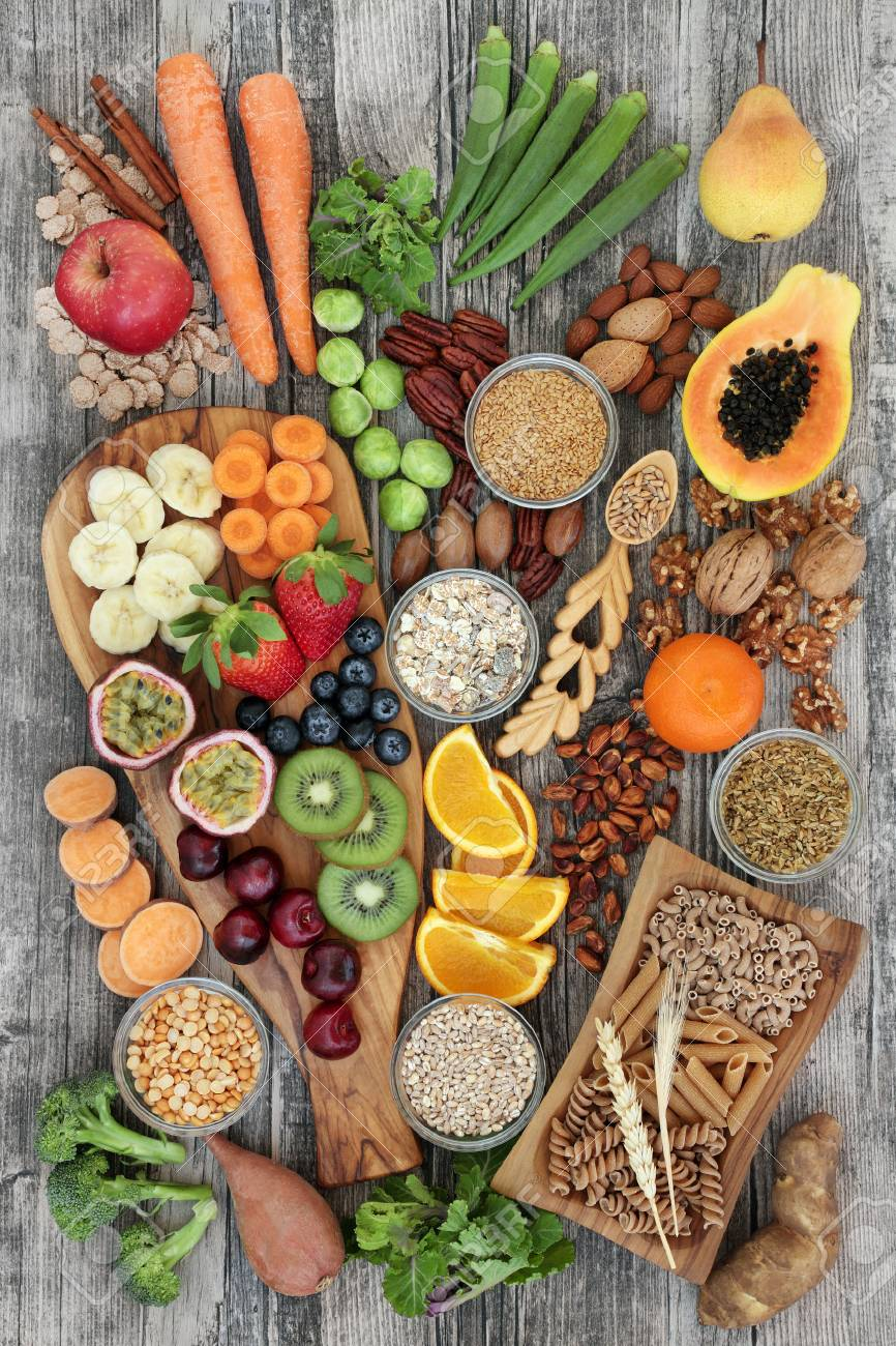 Health food concept for a high fiber diet with fruit, vegetables, cereals, nuts, seeds, whole wheat pasta, grains, legumes and spice. Foods high in omega 3, anthocyanins, antioxidants and vitamins on rustic background top view. - 88628408