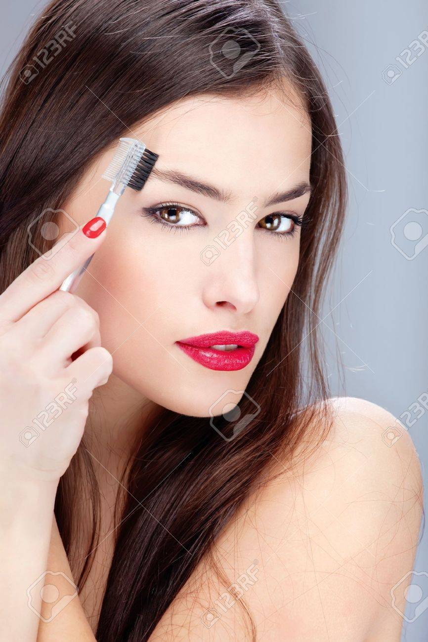 Pretty young woman combing her eyebrow Stock Photo - 12368867