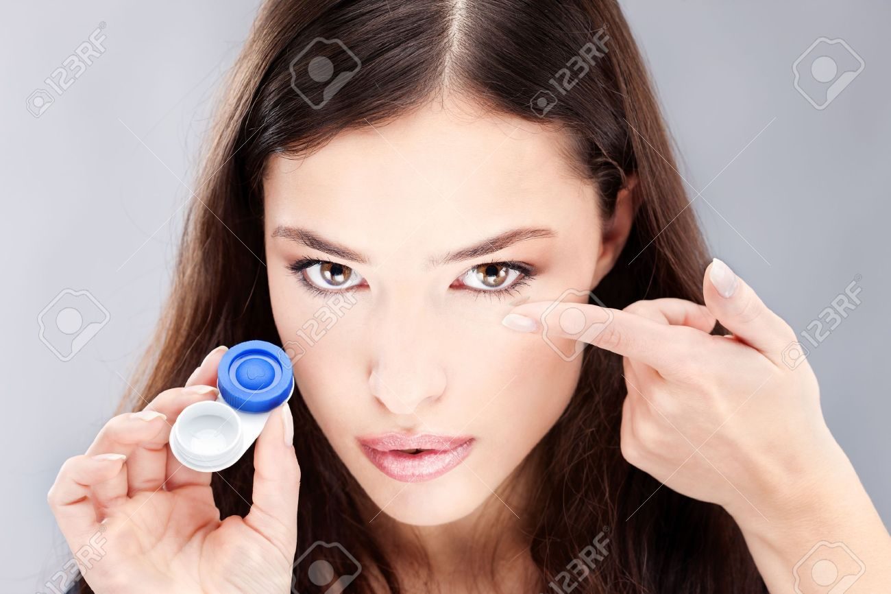 Young woman holding contact lenses cases and lens in front of her face Stock Photo - 12369473