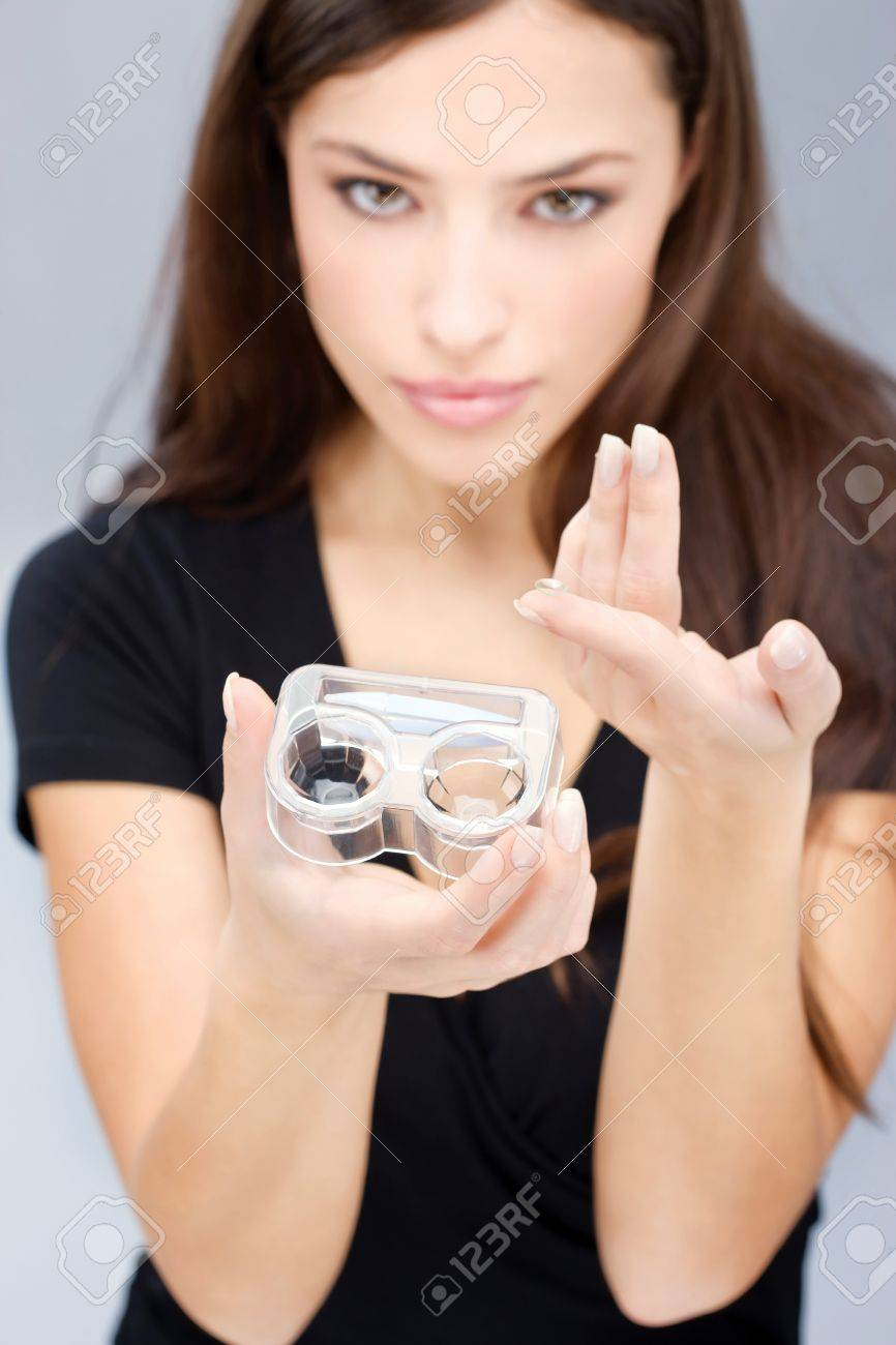 Young woman holding contact lenses cases and lens in front of her. Focus on lens and container. Stock Photo - 12369321