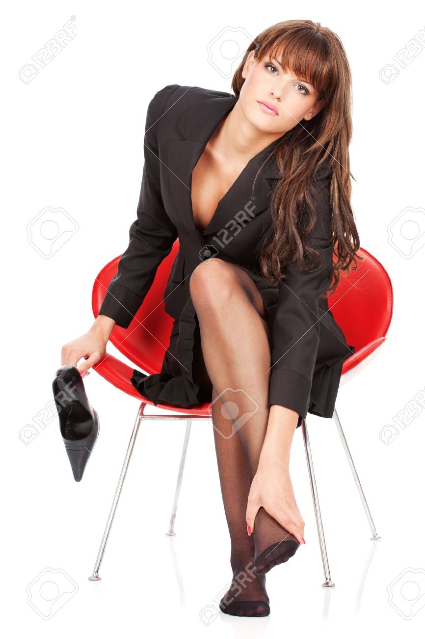 Attractive girl give herself foot massage and looking in camera, isolated on white background Stock Photo - 12369956