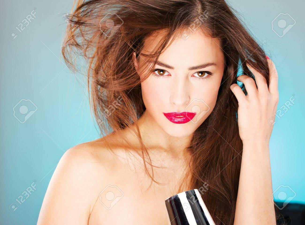 pretty woman with long hair holding blow dryer Stock Photo - 12789345