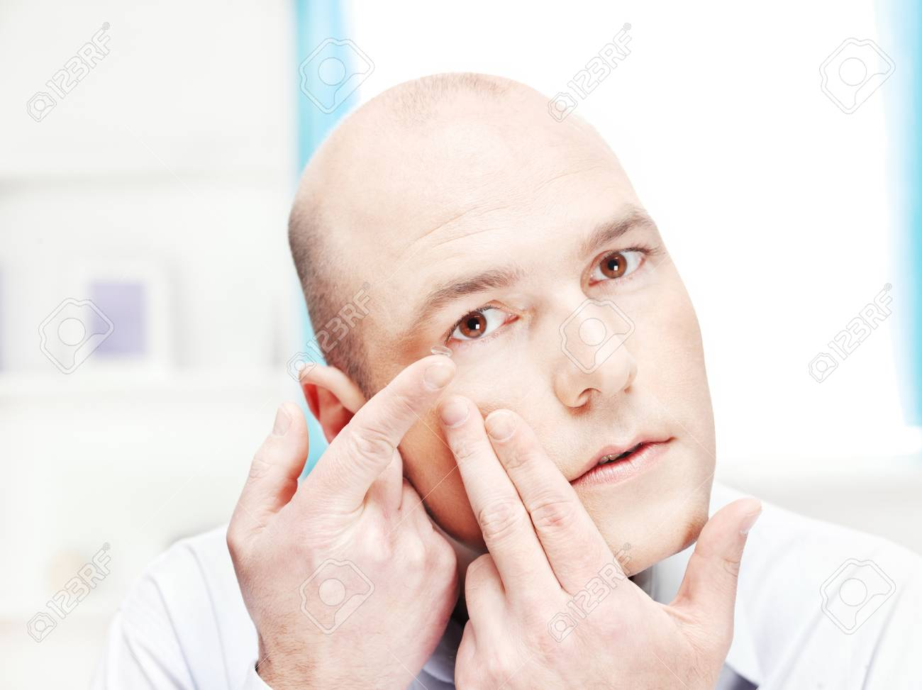 Close up of a man putting contact lens in his eye at home Stock Photo - 13551741