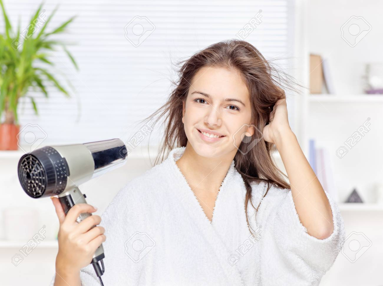Young woman drying hair at home Stock Photo - 16522752