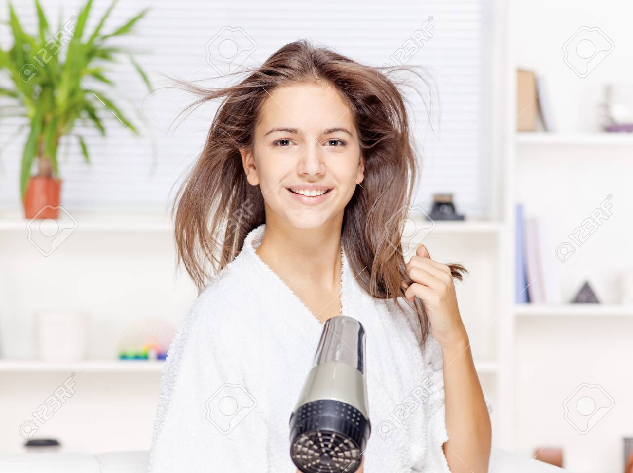 Young woman drying hair at home Stock Photo - 16577600