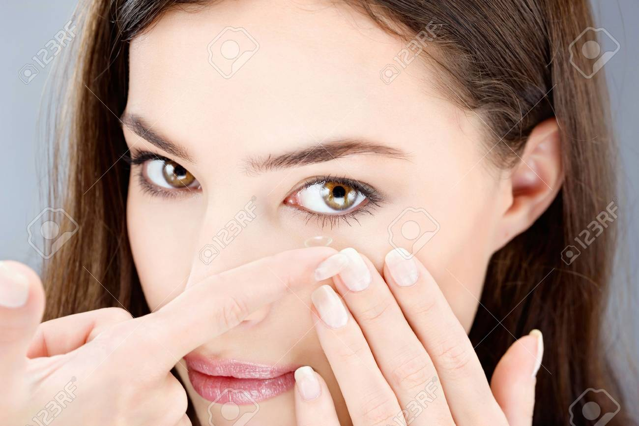 Close up of a woman putting contact lens in her eye Stock Photo - 17107347