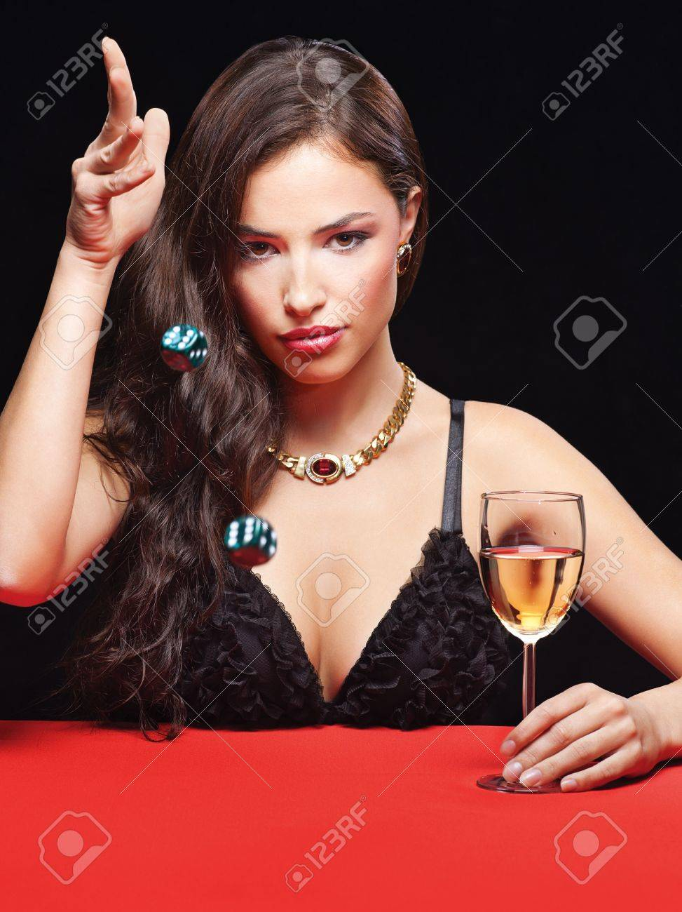 pretty young woman throwing dices on red table Stock Photo - 17166945