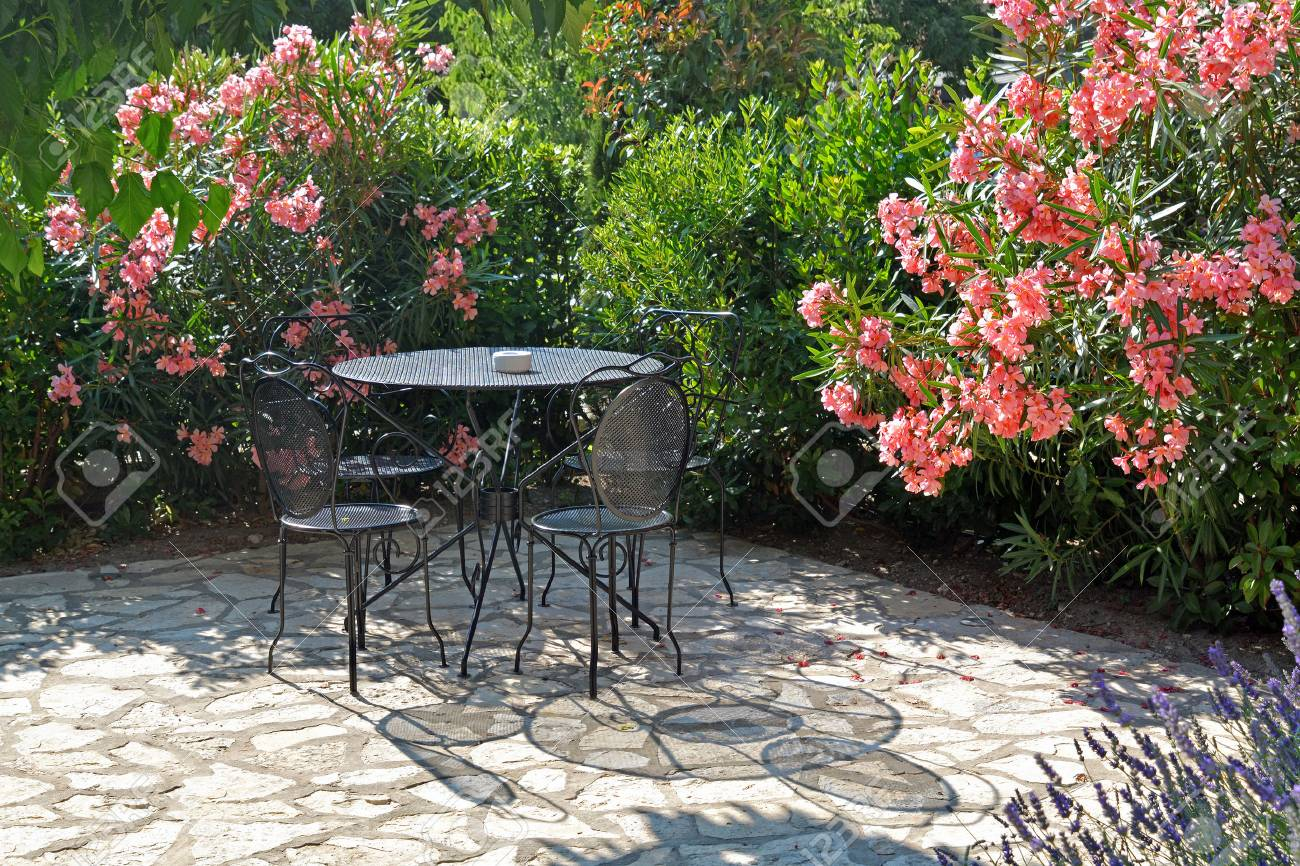 Table and chairs casts a shadow on a summer evening in beautiful flower garden - 53587184