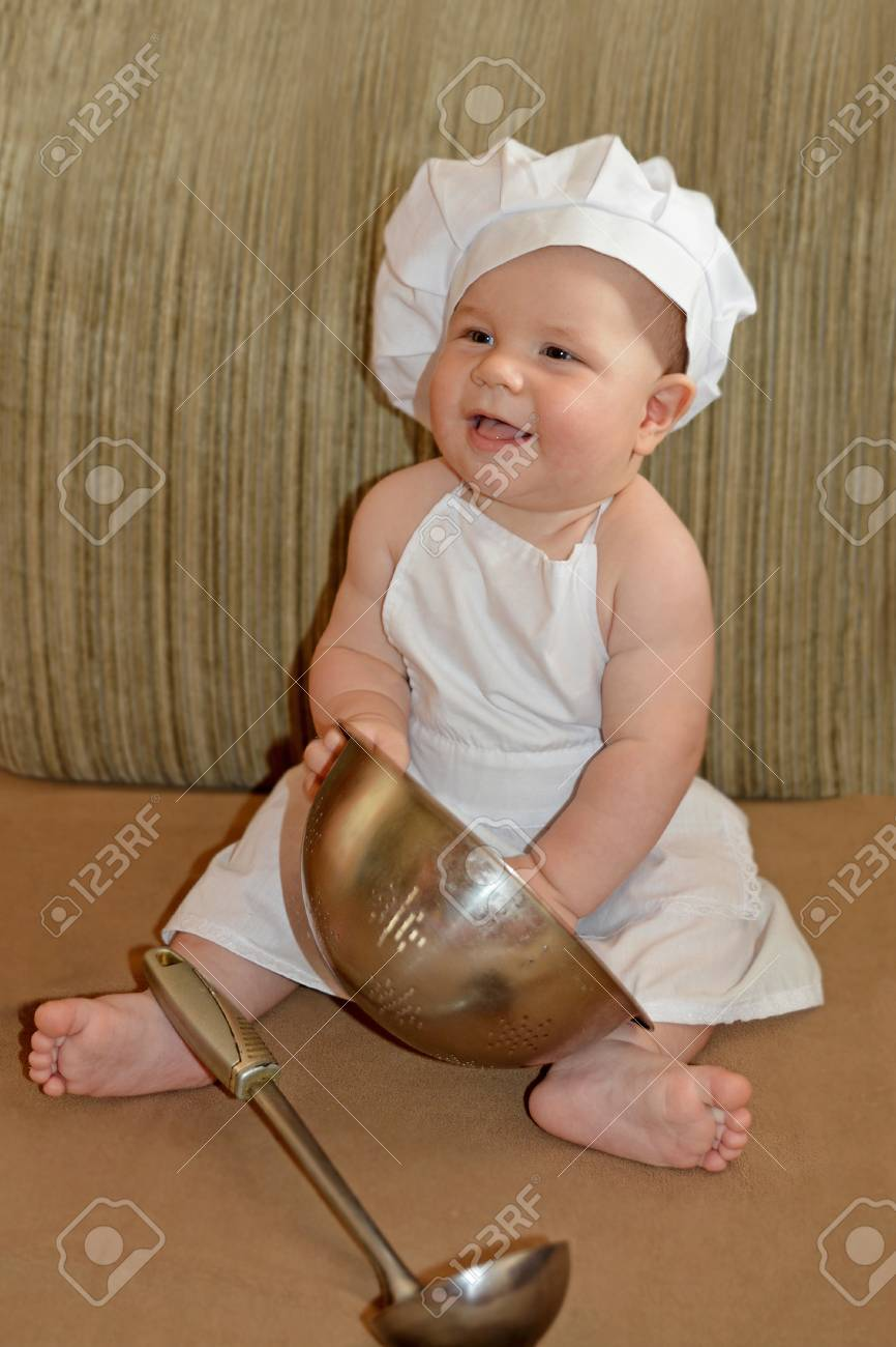 b92d6fcc900 Happy cute little baby in chef hat with kitchen accessories. Stock Photo -  53587715