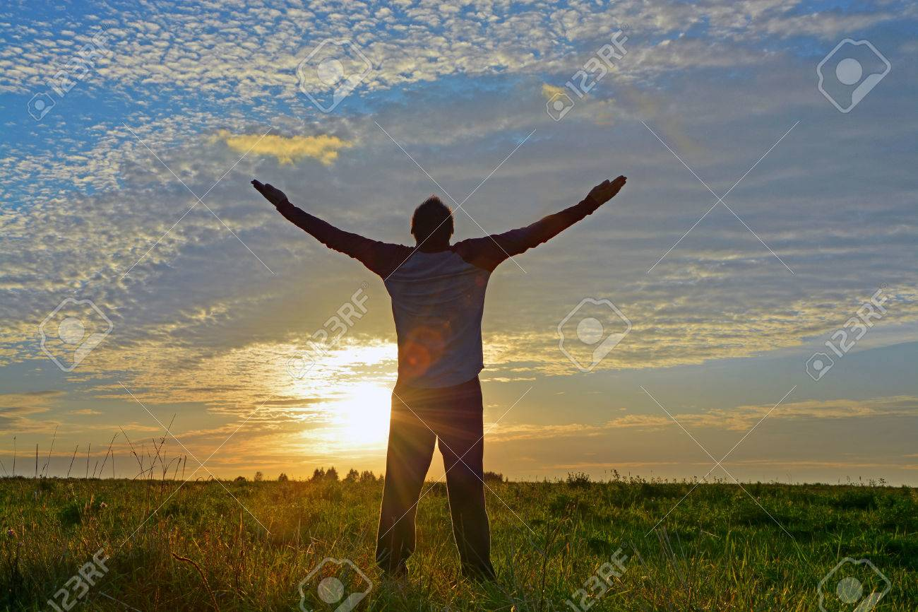 Silhouette of a man with hands raised enjoying his freedom. Concept for religion, worship, freedom - 53591175