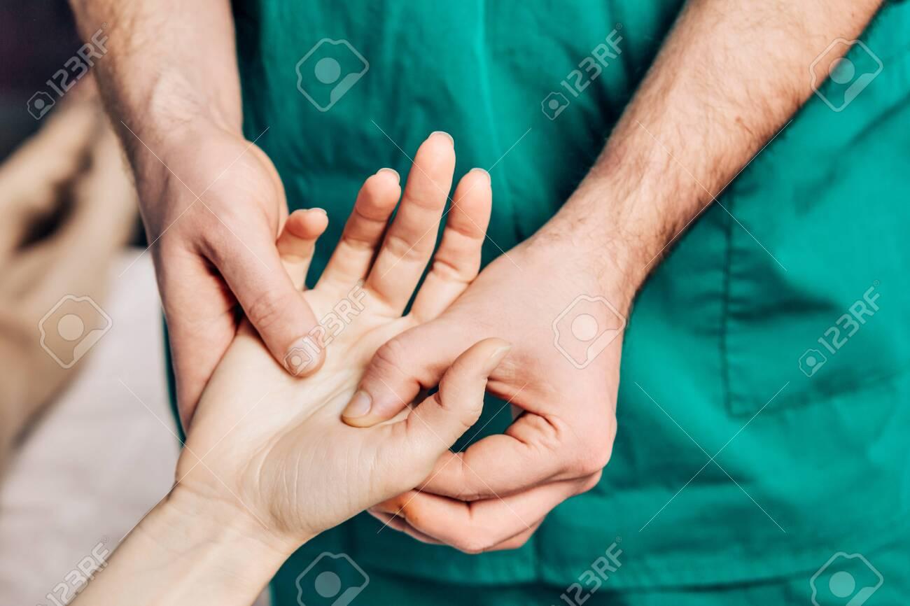 Wrist massage. A male massage therapist puts pressure on a sensitive point on a hand. - 139619218