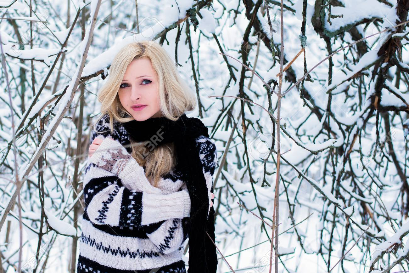 5e97d3ef83 Beautiful young woman with blond hair is dressed in a warm black and white  sweater and