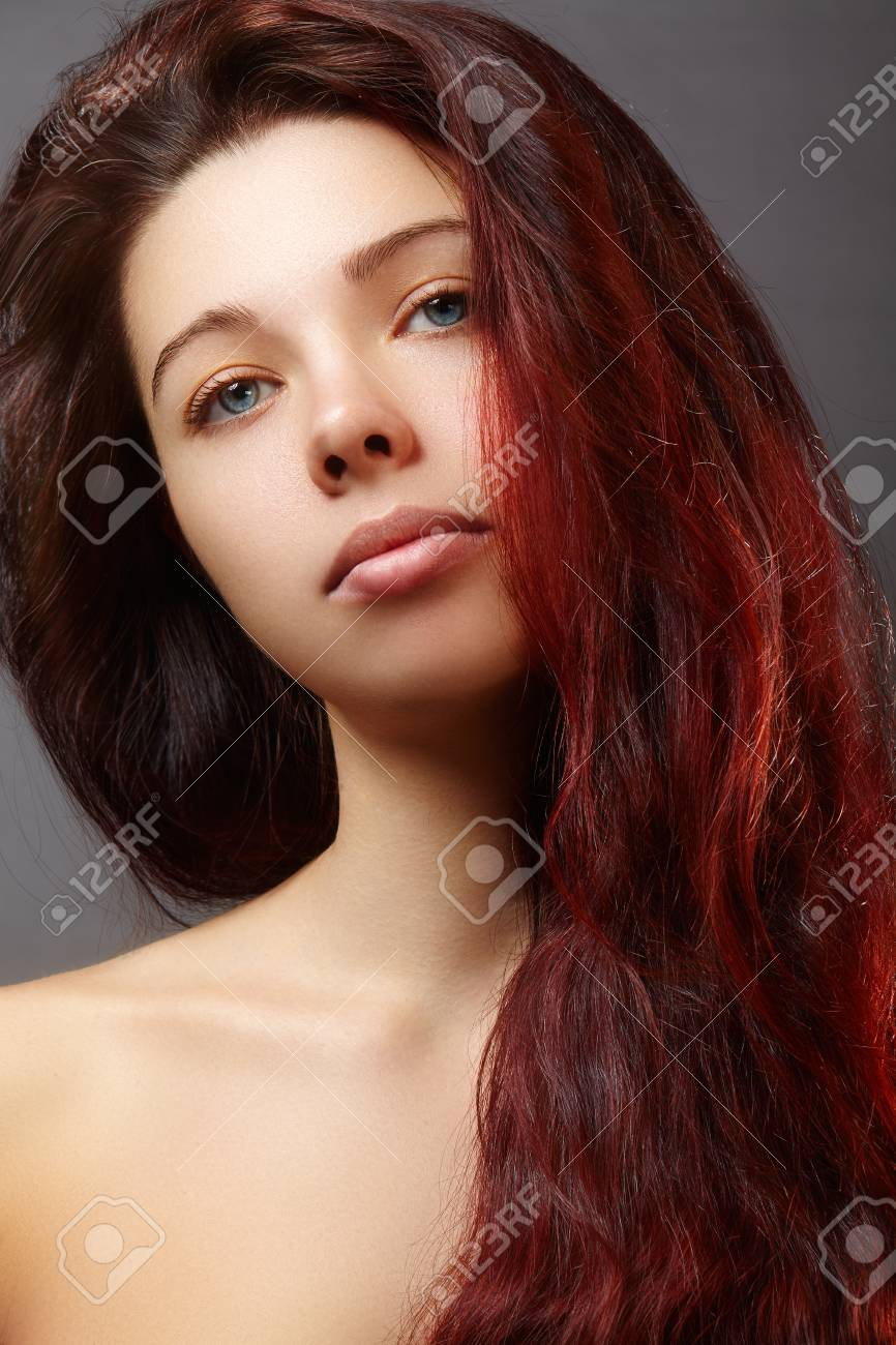 Beautiful ginger young woman with luxury hair style and fashion gloss makeup. Beauty portrait of