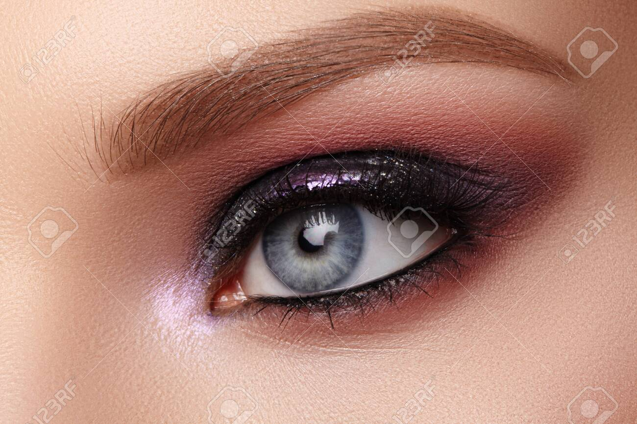 Beautiful Closeup Eye Make-up with Purple Glitter Shadows. Fashion Celebrate Makeup, Glowy Clean Skin, perfect Shapes of Brows. Shiny Shimmer - 138199915