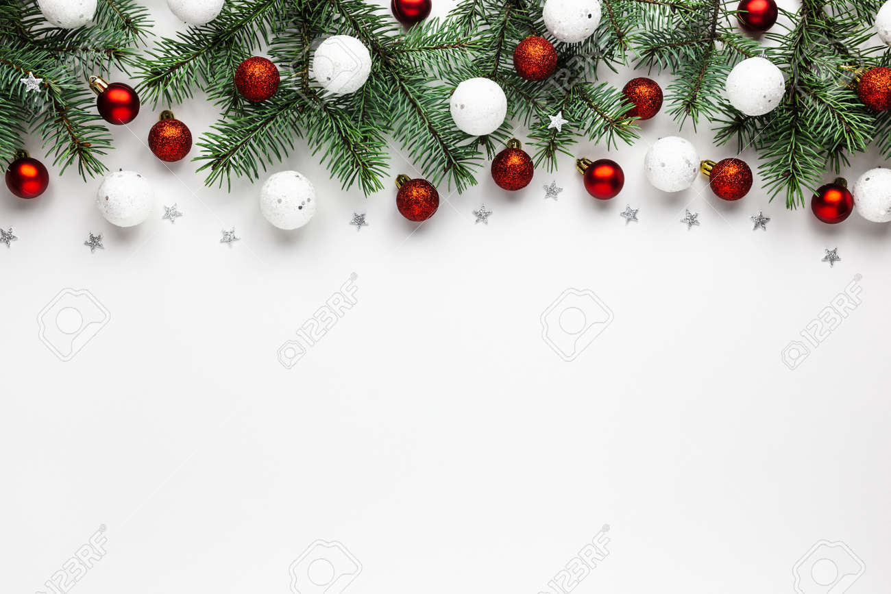Christmas border of shiny white and red balls, evergreen branches on a white wooden background. New year card. - 158910123