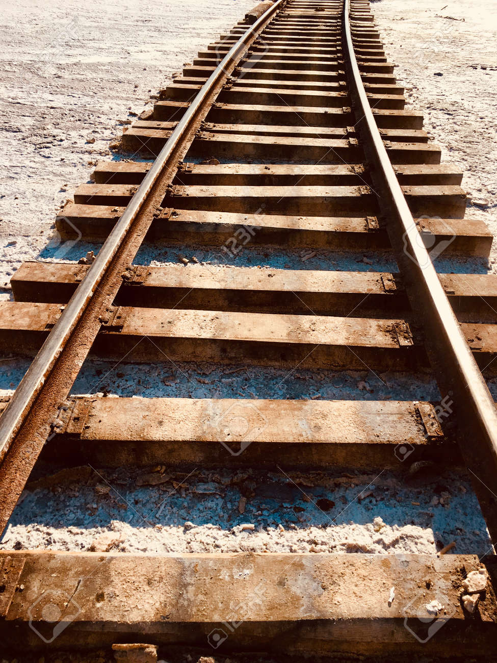 sleepers and rails run along the ground that is covered with white salt - 161122599