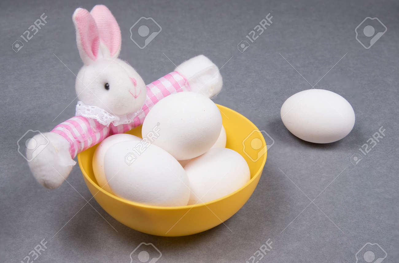 160592914 easter eggs and bunny rabbit on gray background colors of year 2021 gray and illuminating yellow