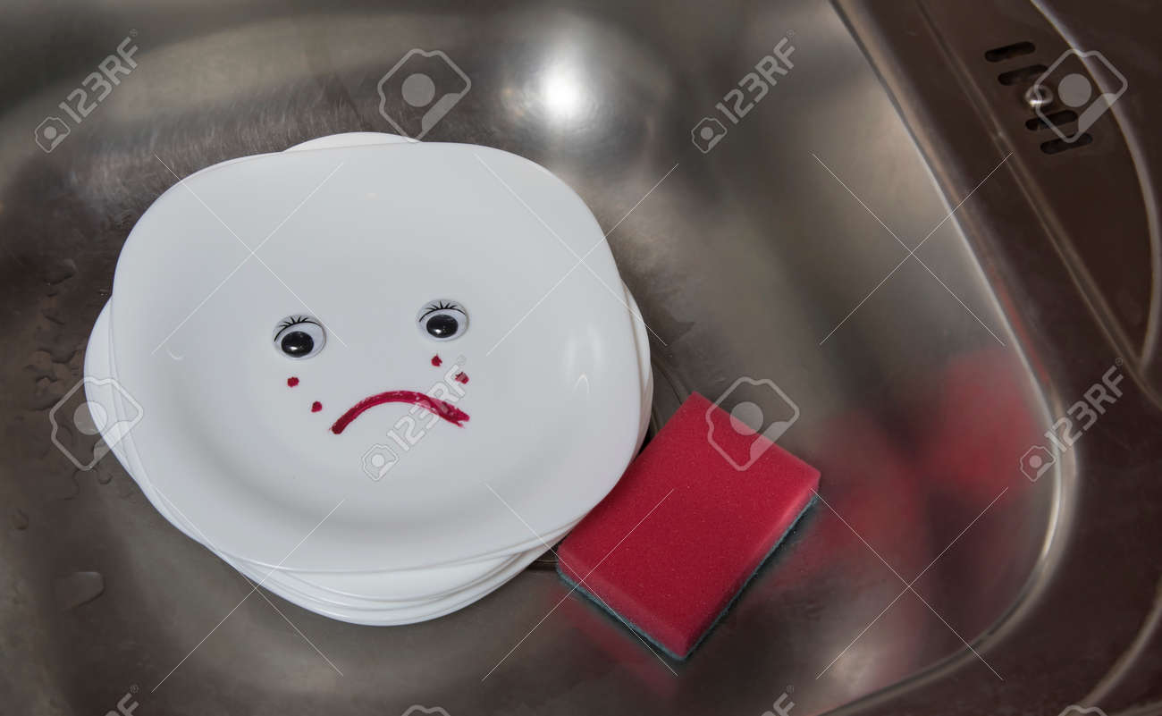 Poorly washed dishes in kitchen sink. White plate with eyes and sad emotion. - 161643510