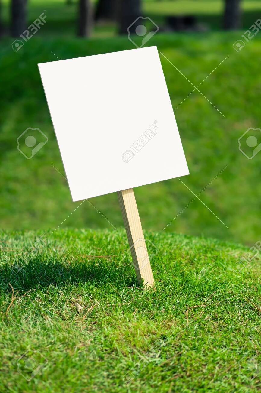 Empty white sign board on a small hill with freshly cut green grass and meadow in the background - 131921527