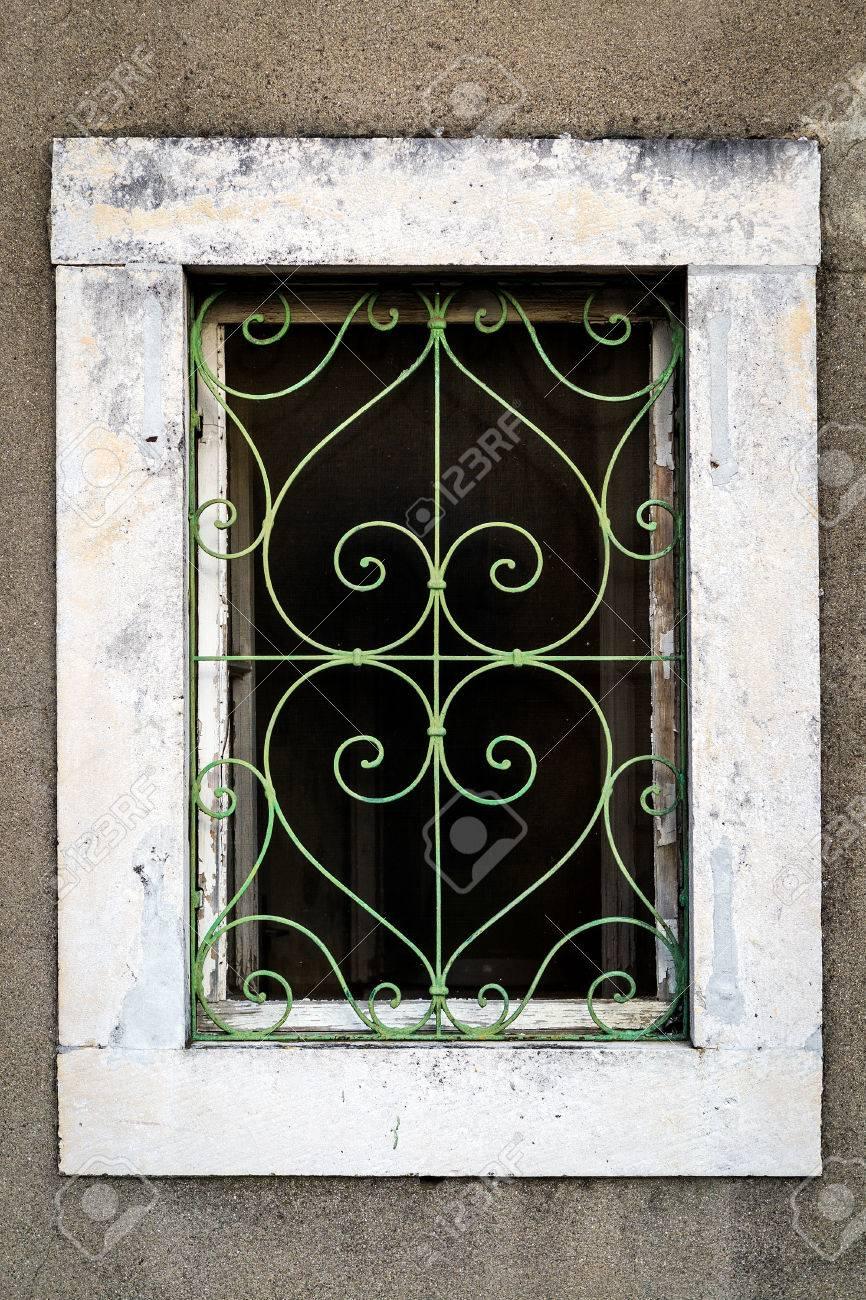 Rusty Green Metal Window With Decorative Bars
