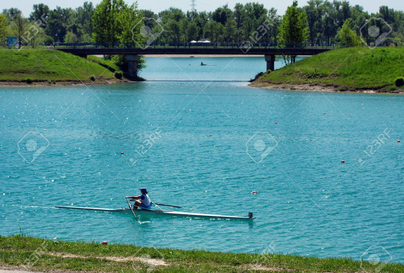 Young girl rowing on lake Jarun, bridge in back, Croatia Stock Photo - 13652659