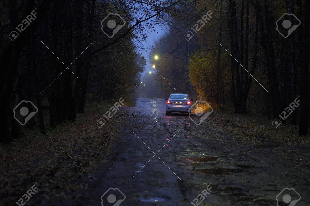 car with headlights on the autumn road - 131922262