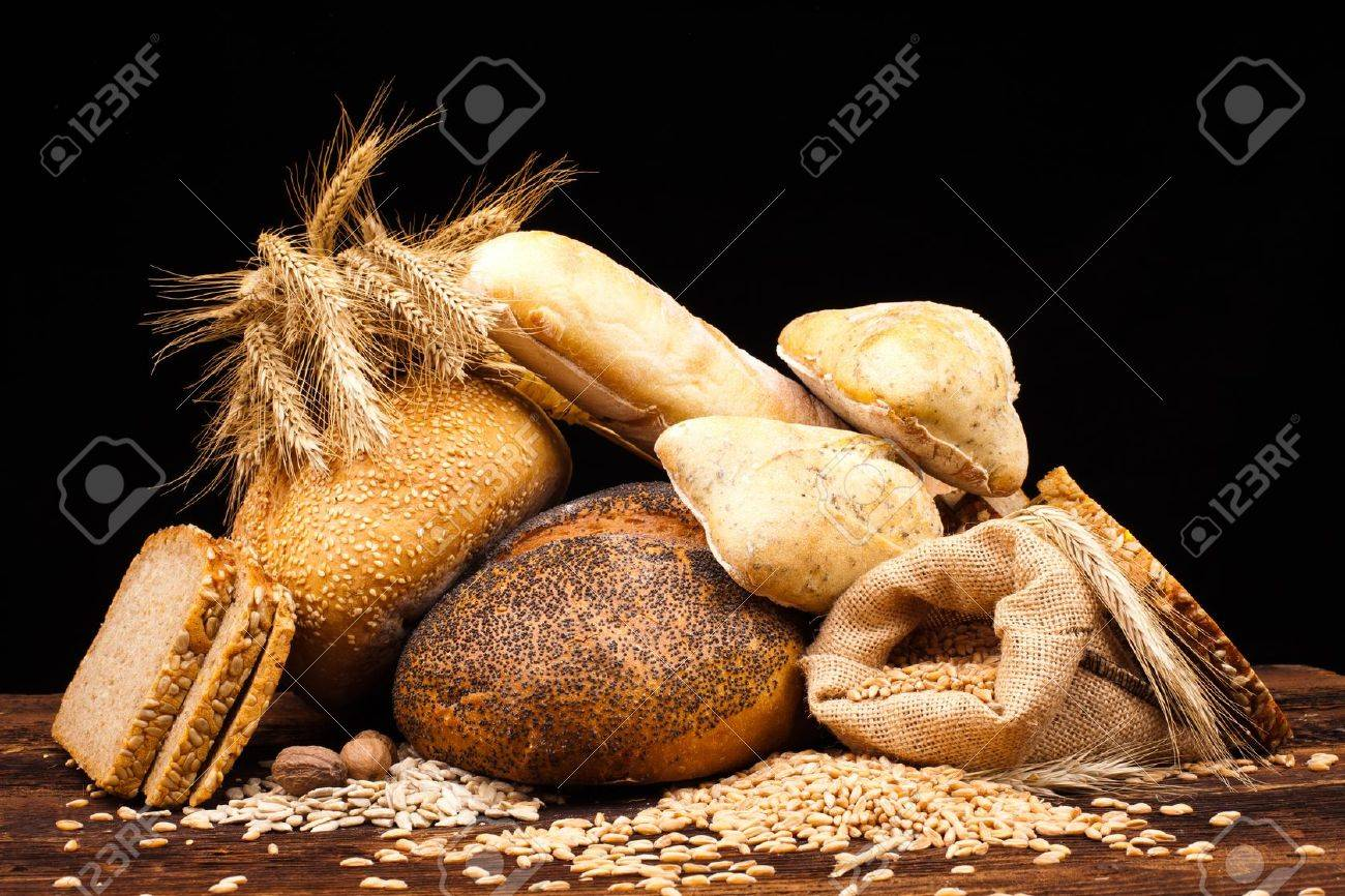 assortment of baked bread on wood table and black background - 16697199