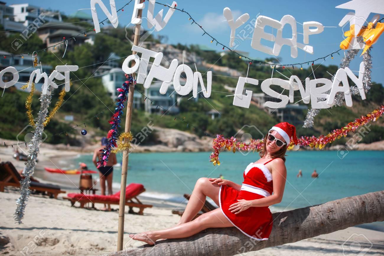 Femme Mignonne En Robe Rouge, Lunettes De Soleil Et Chapeau De Santa Assis  Sur Palmier à La Plage Tropicale Exotique. Concept De Vacances. Koh Samui,  ...
