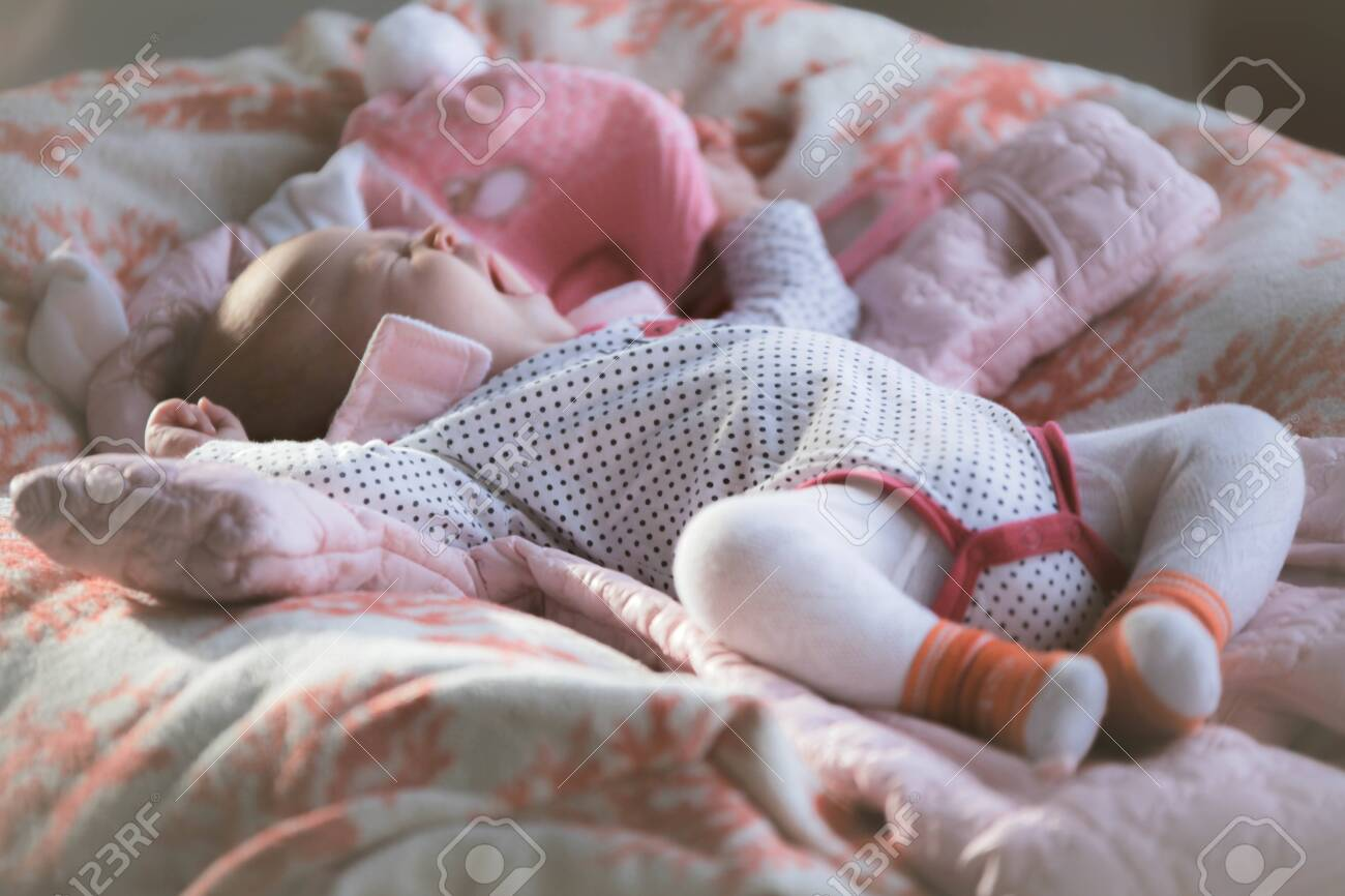 Cute little baby laying on back yawns on the soft cover - 121465008